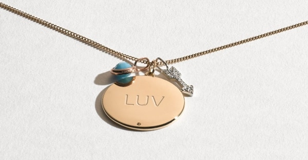 Una collana color oro con ciondolo, incisione LUV e vari charm.
