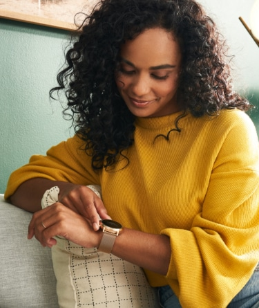 A woman checks a message on her Gen 5 smartwatch