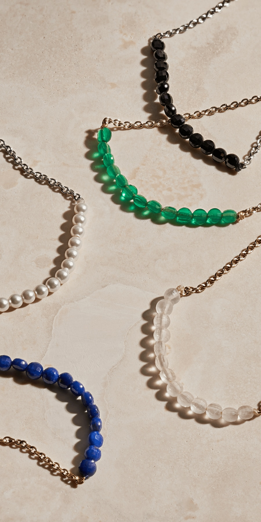 Five necklaces with wellness beads.