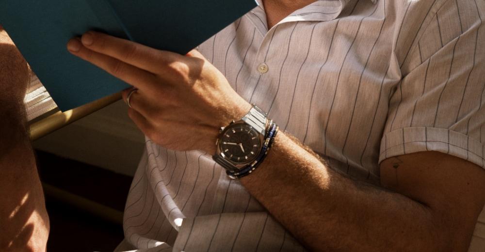 A man wearing an Everett watch reading a book.