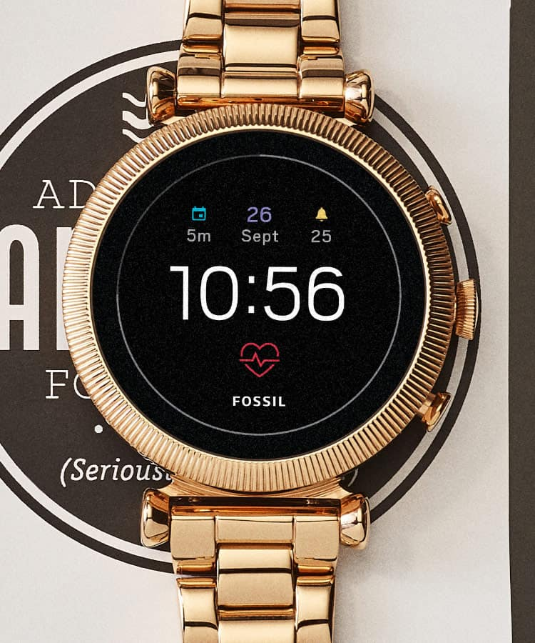 A gold-tone Gen 4 smartwatch displaying the time, date and heart rate on its homescreen.
