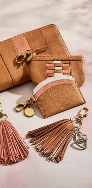 A collection of brown leather wallets with pink accents.