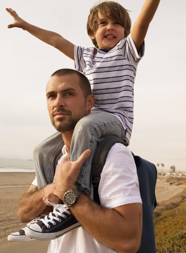 Un garçon les bras croisés sur les épaules de son père.