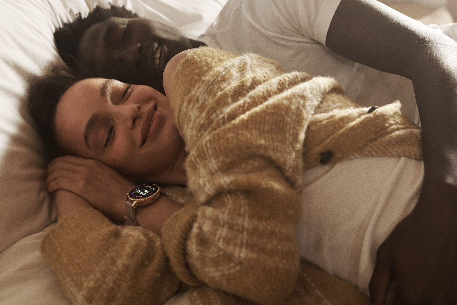 A man and a woman taking a nap with a Gen 6 smartwatch showing colorful charging rings. .