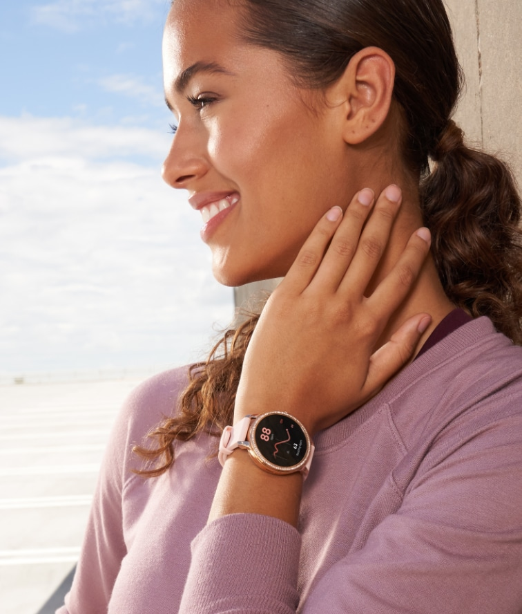 A woman wears a Gen 5E smartwatch.