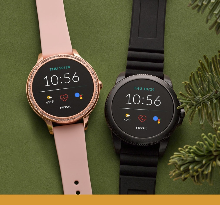 Two Gen 5E Smartwatches on a green background with evergreen pine needles