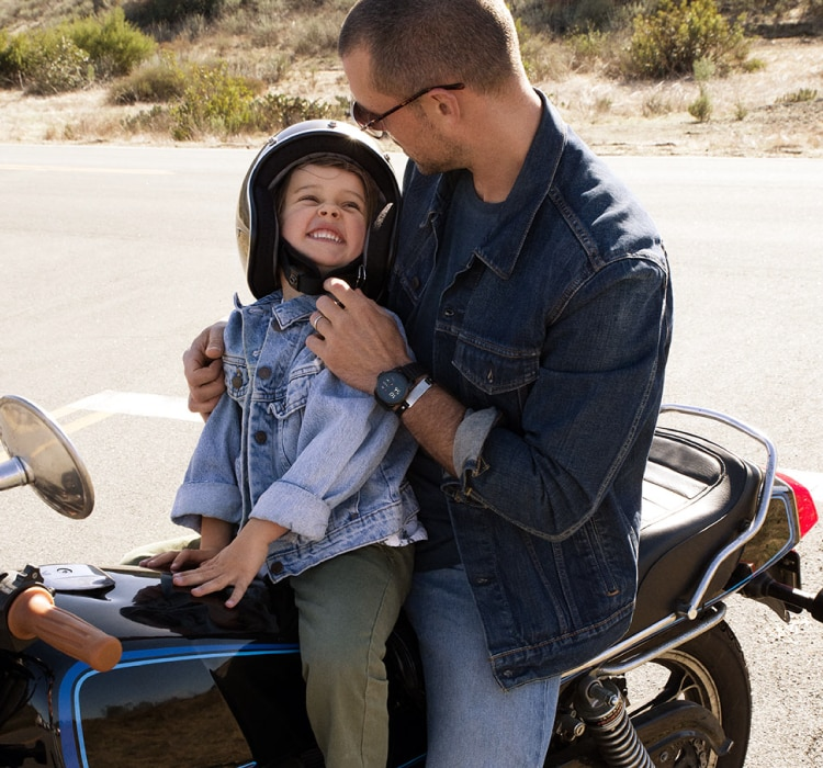 Gif of a dad and his son on a motorcycle and skateboard.