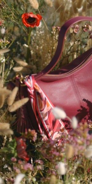 Un sac à main Jolie rouge dans un champ de fleurs.