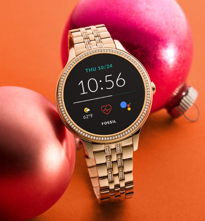 Women's gold-tone Gen 5 Smartwatch on a orange background.