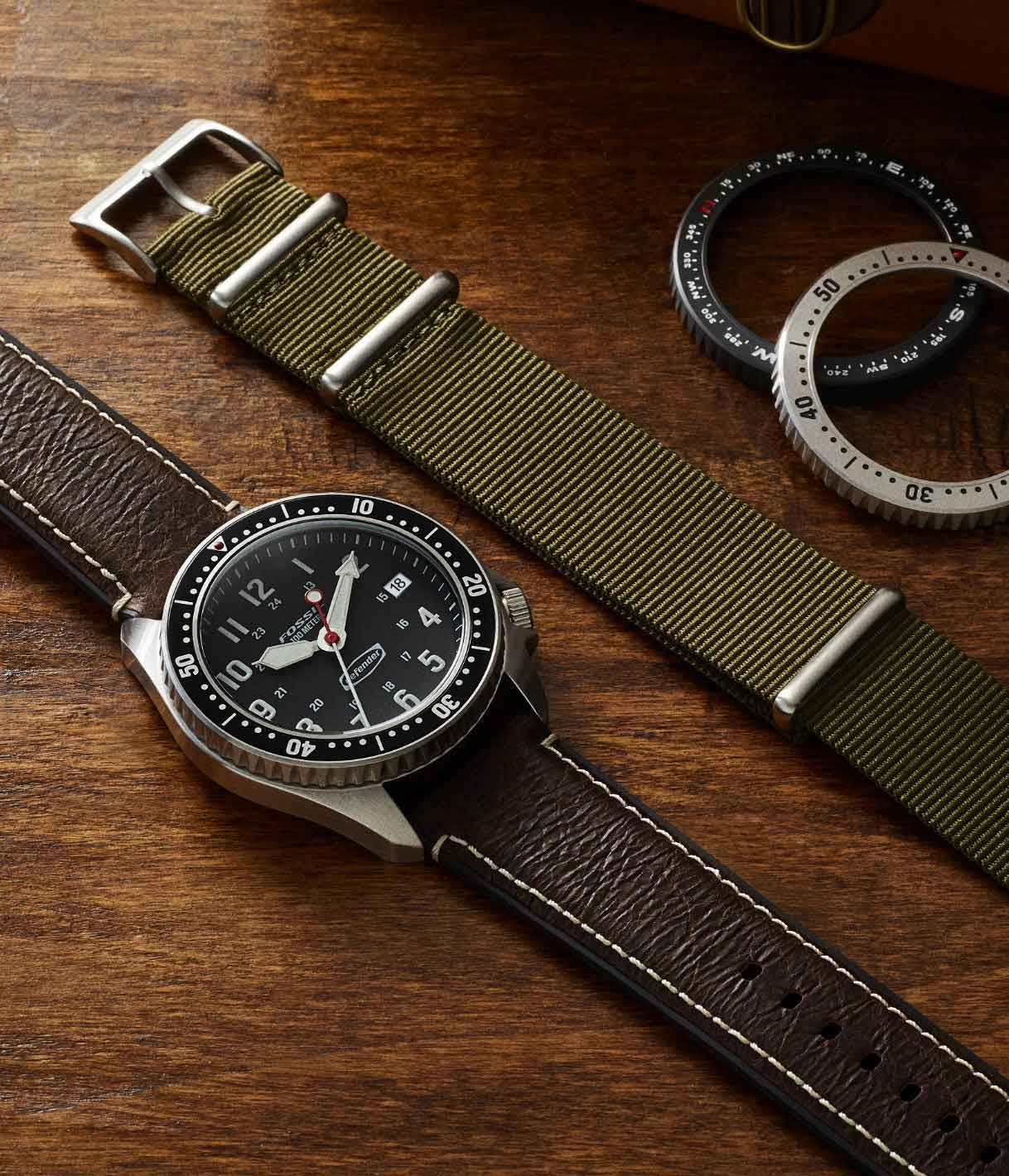 Defender watch beside extra strap and bezels.