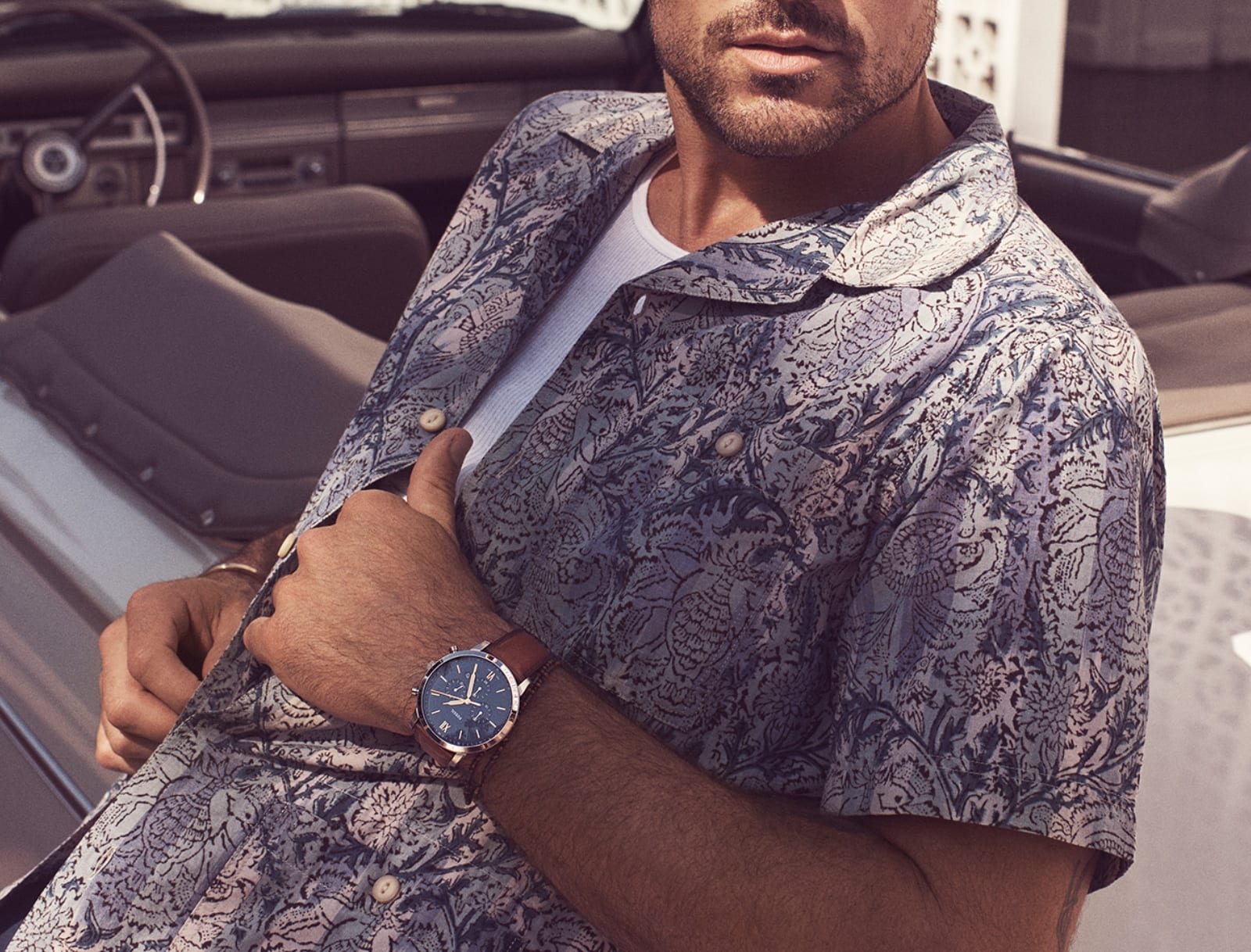Man in patterned shirt with brown leather watch.
