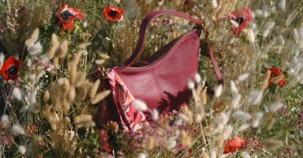 A red Jolie handbag in a field of flowers.